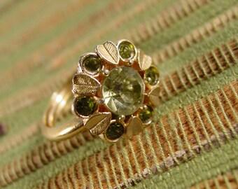 "1974 vintage Avon ""Sun Brilliants"" gold tone ring with green stones"