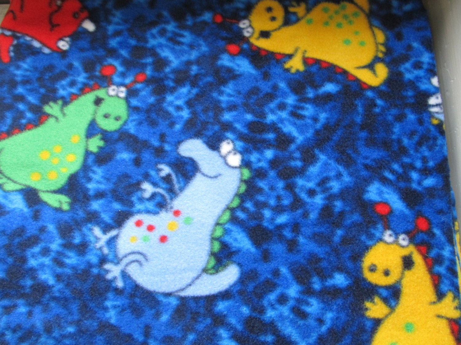 Dinosaurs fleece fabric red yellow green white red dinos for Baby dinosaur fabric