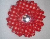 Red gingham checked flower on alligator clip with teeth.