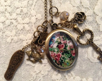 Steampunk Necklace Pendant Pocket Watch. It is antique Bronze with a Beautiful Floral Display on the Face.
