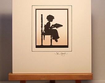 Girl On Chair Reading Hand-Cut Papercut