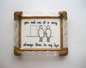 Very Strange Time cross stitch -- inspired ironic, simple cross stitch, minimalist with two people and some buildings