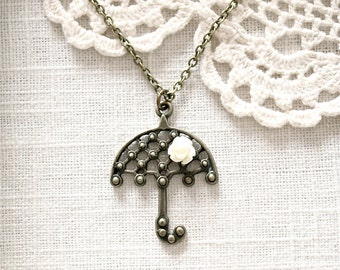 Antique brass umbrella necklace with a small ivory rose flower.  Perfect for Spring.