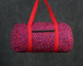 Quilted Duffle bag in Red with Purple Print.