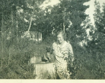Woman Standing With Little Dog on Tree Stump 1920s Lake Side Cottage Camp  Vintage Photo Black and White Photograph