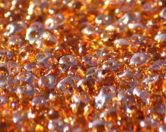 10 grams of 2,5 mm x 5,0 mm sized Topaz Celsian SuperDuo two hole beads (SD027)