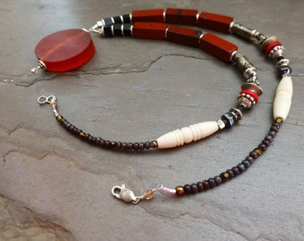 Red Stone and Resin Pendant Necklace: brown, cream, carved bone, hematite, silver tone metal, circles, rectangle red stone, black wood cubes