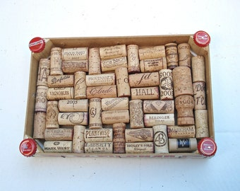 Wine cork board made from a strawberry crate, embellished with beer caps