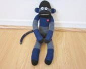 Rugby stripe sock monkey plush with heather gray, black, and navy blue stripes and red heart