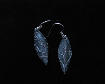 Folded, leaf shaped, silver dangle earrings with tree branch motif highlighted by a deep blue iridescent patina.