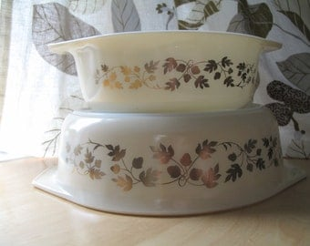 two pyrex cream and gold acorn casserole dishes
