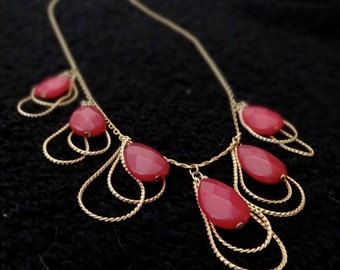 Necklace with teardrop shaped faceted red plastic beads encircled by double gold tone chains