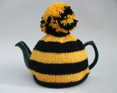 Striped tea cosy gold and black with a pompom for a medium pot.