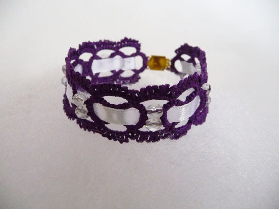 Handcrafted purple bracelet  with beads and ribbon.