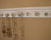 "Necklace organizer. This jewelry hanger has 7  knobs features large rhinestone center on gloss white background 20 "" long. wal storage rack"