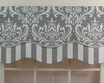 Layered shaped valance in grey damask over stripe with gimp trim