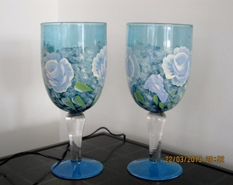 A set of blue glasses with white roses green leaves and baby breath comes with matching tile coasters hand painted