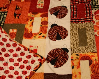 Cute Ladybug Quilt in bright oranges. Appliqued ladybugs dance on the top