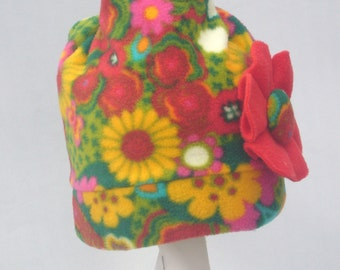 Children's flower patterned fleece hat with red flower at side.