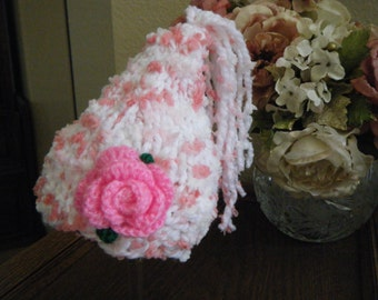 Nubby knit pixie newborn hat in pink and white with tassels and pink flower.