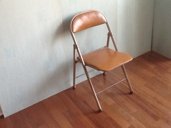 A vintage industrial metal folding tan colored chair American