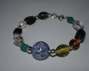 Bracelet with multi colored beads and a beautiful larger focal bead of swirled blue, purple and white.