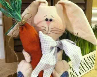 Country Primitive Easter and Spring sitting Bunny Rabbit with floppy ears and big feet holding a large carrot