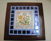 Ceramic floral trivet trimmed in blue glass tile and mahogany