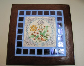 Ceramic floral trivet trimmed in blue glass tile and mahogany