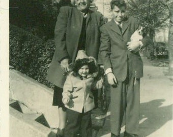 Boy Holding New Puppy Dog With Little Brother and Grandmother Standing Outside 1940s  Black White Vintage Photo Photograph