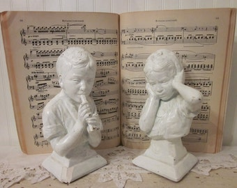 vintage ESCO busts. Boy plays flute, Girl covers ears. E. Villanis. Rustic shabby chippy white mid-century children music statues bookends