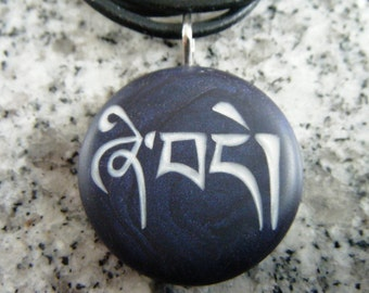 Tibetan-Peace Pendant hand carved on a polymer clay midnight blue pearl color background.  Comes with a FREE necklace