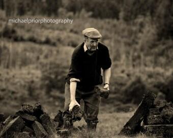 old man stacking turf in connamara