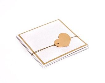 Handmade custom romantic folded wedding invitation, embossed background and beige heart.
