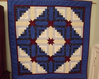 A Wall Quilt  in a traditional design in blues, neutrals and burgundy