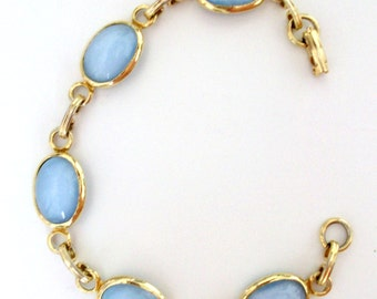 vintage blue glass bracelet with a opaline or  moonstone look. Set in golden tone.  7""