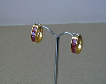 A pair of gold earings with faux rubbies
