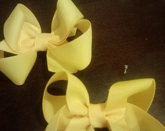 Pair of yellow pigtail bows