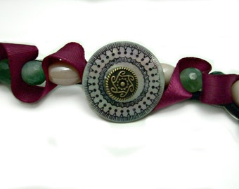 Beaded ribbon headband. Mother of pearl etched button hair accessory. Faceted emerald bead, burgundy ribbon. Elastic headband.