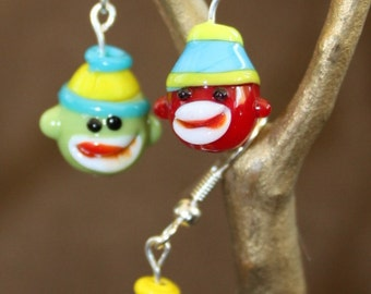 Sock monkey earrings handmade with lampwork glass beads dangle from silverplate wires