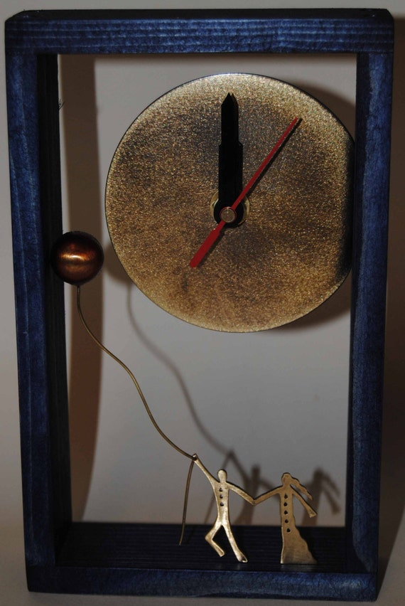 Desk bronze clock with deep blue wooden frame.