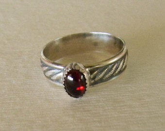 Sterling silver stacking ring with garnet gemstone.