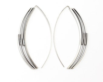 "Pieces of silver woven together in a long arc shape to create an artistic and modern earring design - ""Interlace Earrings"""
