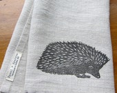 linen tea towel block printed with graphite hedgehog on toast linen