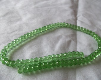 Bead, glass, pale green, 5x4mm-6x4mm faceted rondelle. Sold per 12-inch strand