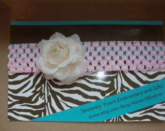 Adorable crochet headband accented with a sweet off white glittery rose
