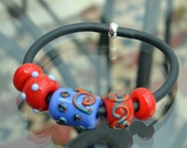 Lampwork coloured beads on rubber tubing.