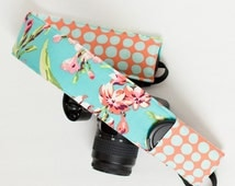 DSLR camera strap cover with lens cap pocket.  Teal and tangerine floral and dot.