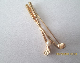 Golf clubs and ball pin in gold finished metal