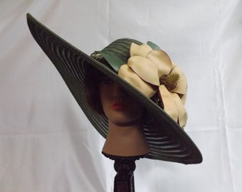Derby straw wide rimmed olive hat with an exotic flower with bulbs and foliage.